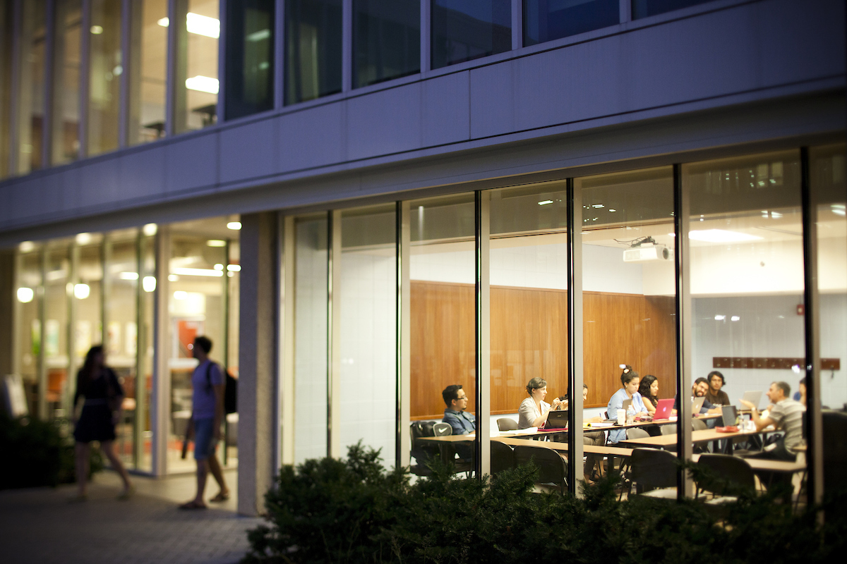 an image of a lit classroom at night from the outside
