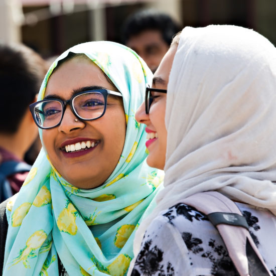 Two students with glasses and headscarves smiling