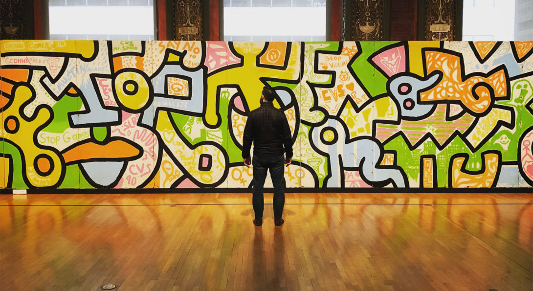 A man stands in front of Keith Haring's