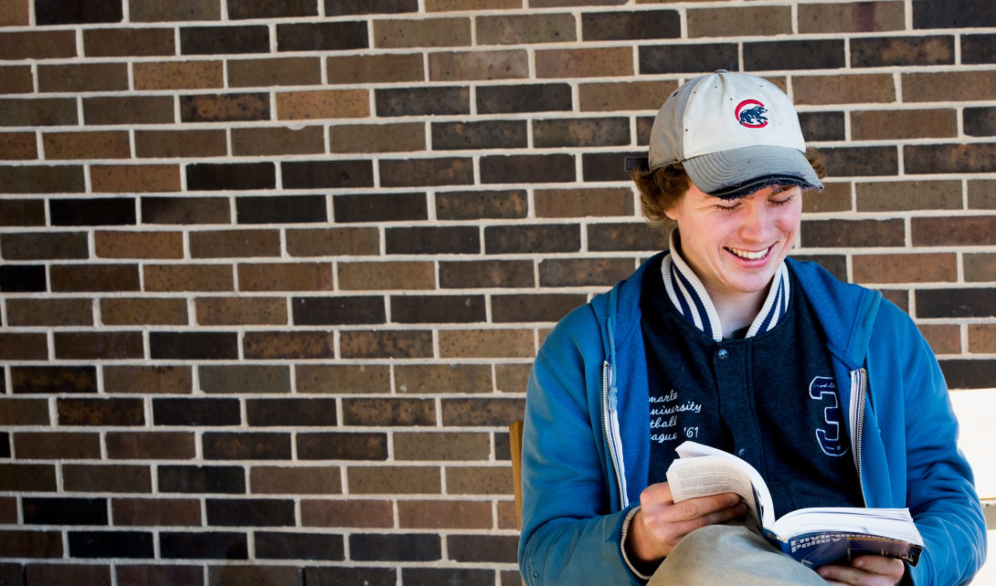 a person wearing a Cubs baseball hat reads a book and smiles