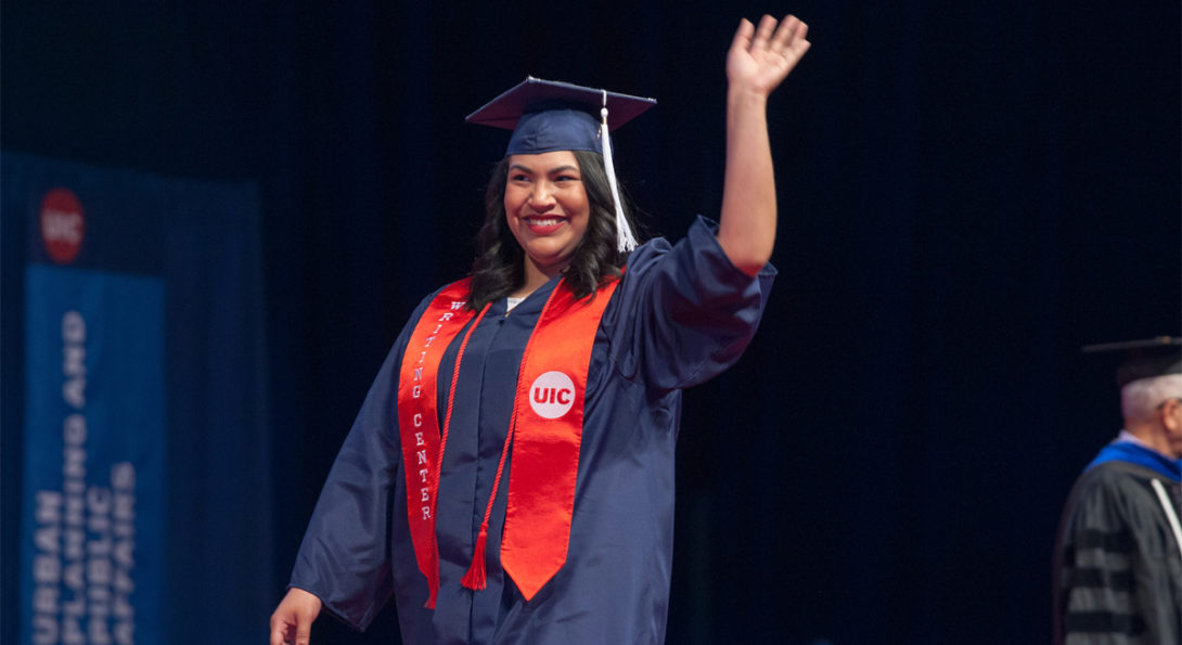 A woman wearing a cap and gown and red sash waves at graduation