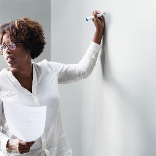 a woman stands at a whiteboard and looks behind her