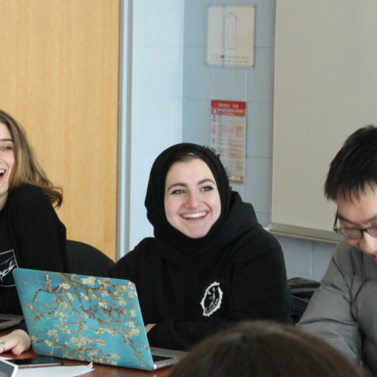 Students laughing in front of their laptops