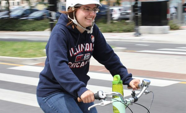 a woman rides a bicycle on the street near UIC