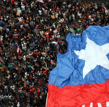 A crowd of protesters are seen from above, partially covered by an enormous Chilean flag