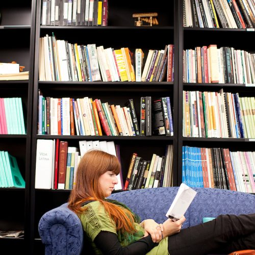 a person reads in front of a bookshelf